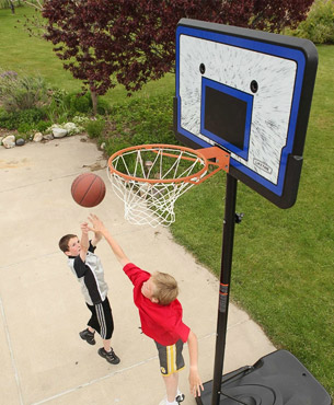two boys shooting a basketball to the Lifetime 1221 portable hoop